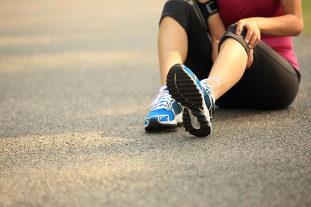 dolor de espalda: Corredor de la mujer se sostiene el deporte al aire libre de la rodilla lesionada