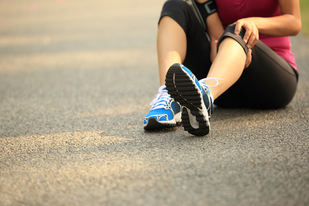 human knee: woman runner hold her sports injured knee outdoor