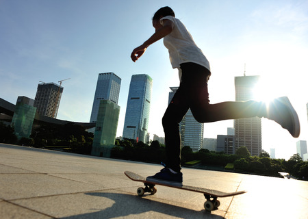 skateboard shoes: woman skateboarder legs skateboarding at sunrise city Stock Photo