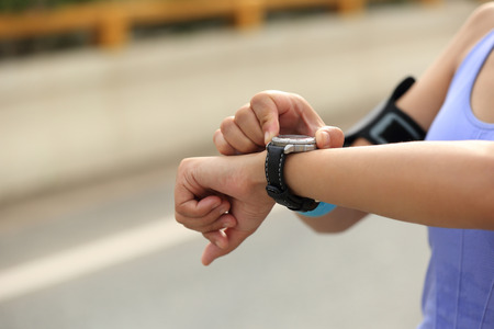 watch: young woman jogger ready to run set and looking at sports smart watch, checking performance or heart rate pulse trace. Sport and fitness outdoors in city. Stock Photo