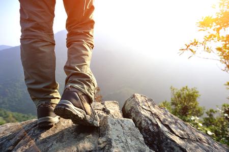 woman hiker stand on mountain peak rock Banco de Imagens