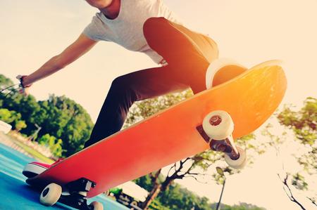 tablero: piernas de la mujer skate en el skatepark Foto de archivo
