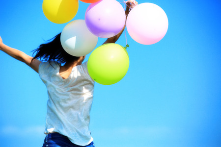 colourful sky: young asian woman running and jumping  with colored balloons