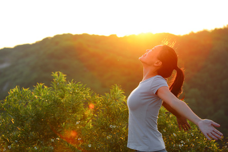 cheering woman open arms at sunrise mountain peak