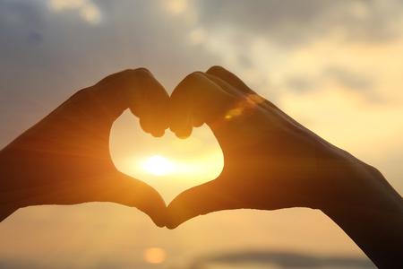 manos: toma la forma del corazón de las manos contra la puesta de sol brillante mar y forma de oro de sol en el agua Foto de archivo