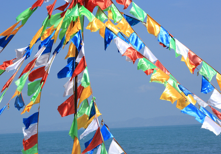 sutras: buddhist prayer flags waving in the wind against blue sky