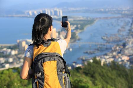 young woman hiker use smart phone taking self photo at mountain peak 免版税图像