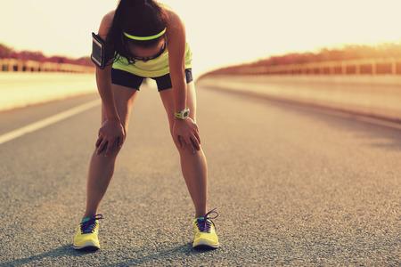 corriendo: Corredor de la mujer cansada de tomar un descanso despu�s de correr duro en el camino de ciudad