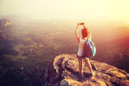 mochila de viaje: Caminante de la mujer que toma la foto con el teléfono inteligente en el acantilado pico de la montaña