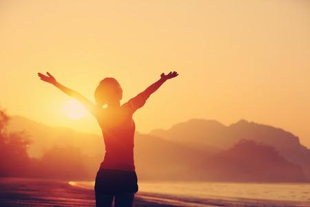 vrouwen: sterk vertrouwen vrouw open armen onder de zonsopgang bij kust