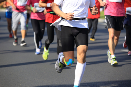 Many marathon runners running on city road