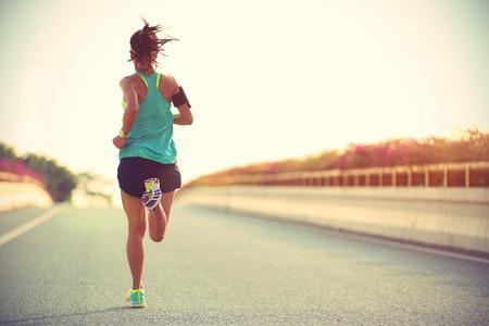 市橋道路で実行されている若い女性ランナー