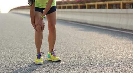 knee: woman runner hold her injured leg on road