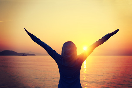 sport silhouette: woman open arms under the sunrise at seaside Stock Photo