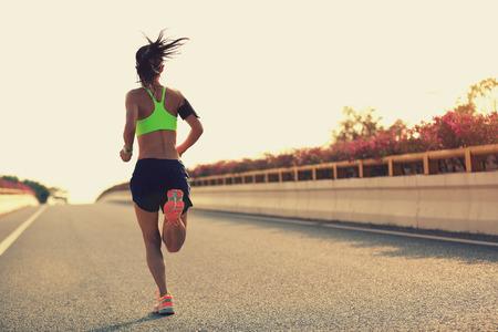 escucha activa: joven corredor de la mujer que se ejecuta en la ciudad camino del puente