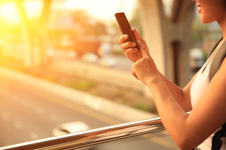 도시에 젊은 여자가 사용 휴대폰 스톡 콘텐츠