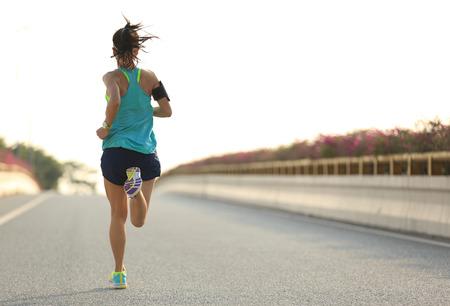 jonge vrouw running on stadsbrug weg
