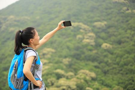 trekker: woman hiker taking photo with smart phone at mountain peak cliff