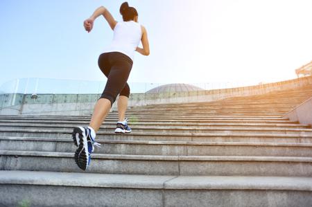 atleta corriendo: Runner atleta que corre en las escaleras. Aptitud de la mujer trotar entrenamiento concepto de bienestar.