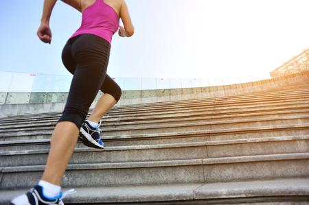 climbing stairs: Runner atleta que corre en las escaleras. Aptitud de la mujer trotar entrenamiento concepto de bienestar.