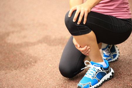 knee: Woman hold her injured knee Stock Photo