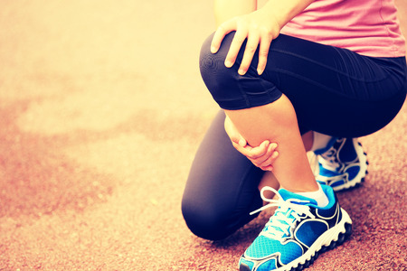 sports injury: woman runner holding her twisted ankle Stock Photo