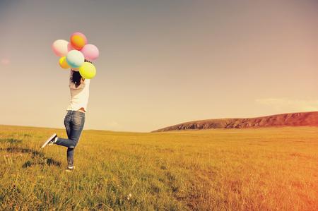 ser humano: mujer asiática joven corriendo y saltando en prado verde con globos de colores