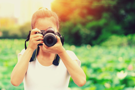 taking photo: Young woman photographer taking photo of blooming lotus at park