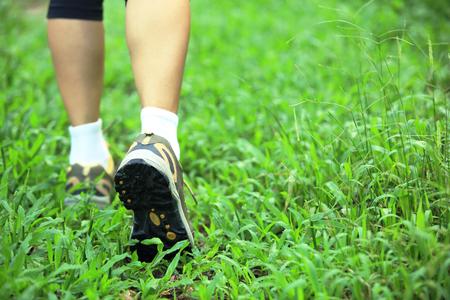 correr las piernas de senderismo en la hierba verde Foto de archivo