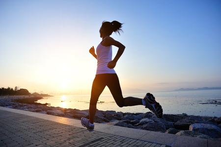 Woman running at seaside. Stockfoto