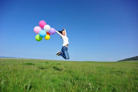 若いアジア女性を実行して色の風船で緑の草原にジャンプ
