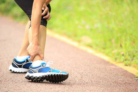 twitch: woman runner holding her twisted ankle Stock Photo