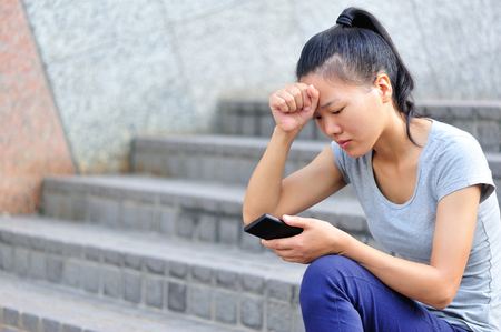 bad news: young asian woman got bad news with her smart phone Stock Photo