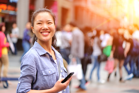 chinese people: Woman holding smart phone on shopping street Stock Photo