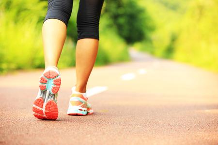 jeunes jambes de femme de remise en forme de marche sur le sentier de la forêt