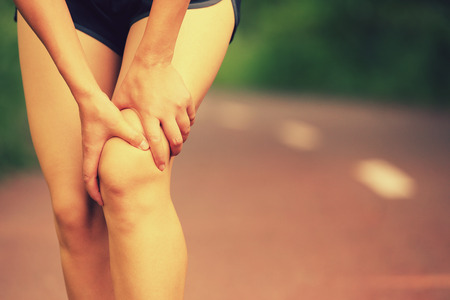 twitch: young woman runner hold her injured leg Stock Photo