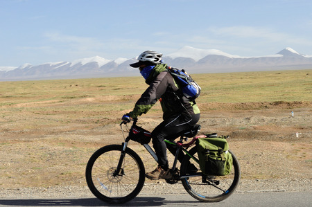 cycling mountain: Tibet, china - July 30, 2014: people cycling mountain bike climbing the mountain road lead to Lhasa city, tibet, china.
