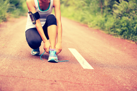 shoelaces: young woman runner tying shoelaces on trail Stock Photo