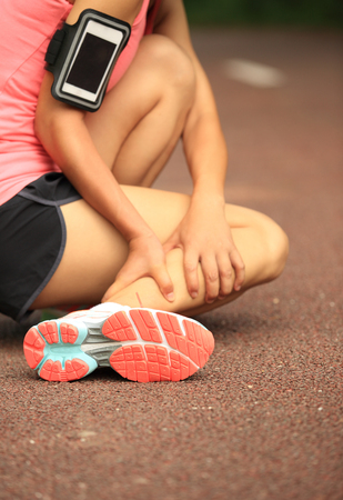 twisted: woman runner holding her twisted ankle Stock Photo