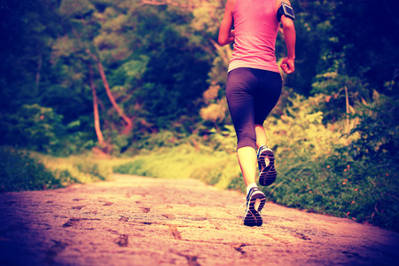 woman street: young fitness woman running at forest trail