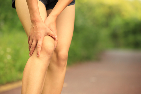sports injury: woman runner hold her injured leg Stock Photo