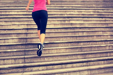 escalera: Mujer que se ejecuta en las escaleras. Foto de archivo