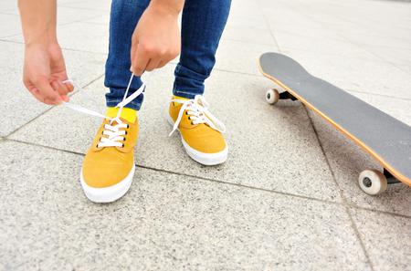 shoelace: skateboarder tying shoelace