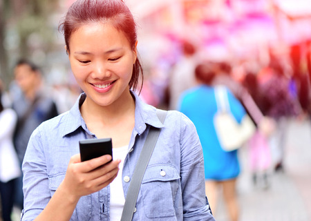 mobile phone screen: beautiful young asian woman using smart phone on shopping street Stock Photo