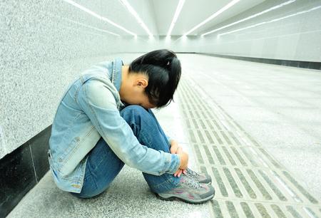teleurgestelde vrouw zitten op de passage van metrostation Stockfoto