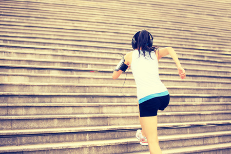 woman running: Runner athlete running on stairs. listening to music in headphones from smart phone mp3 player smart phone armband.woman fitness jogging workout wellness concept.