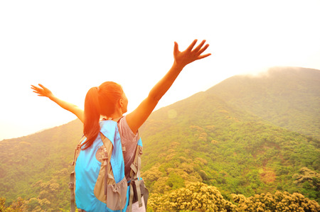 woman hiker open arms to mountains 写真素材
