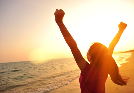 winning: cheering woman open arms at sunset seaside beach