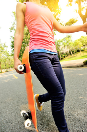 fitness young woman walking with skateboard in hands 版權商用圖片