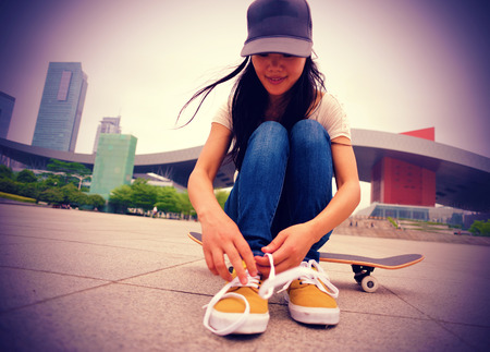 young woman skateboarder tying shoelace